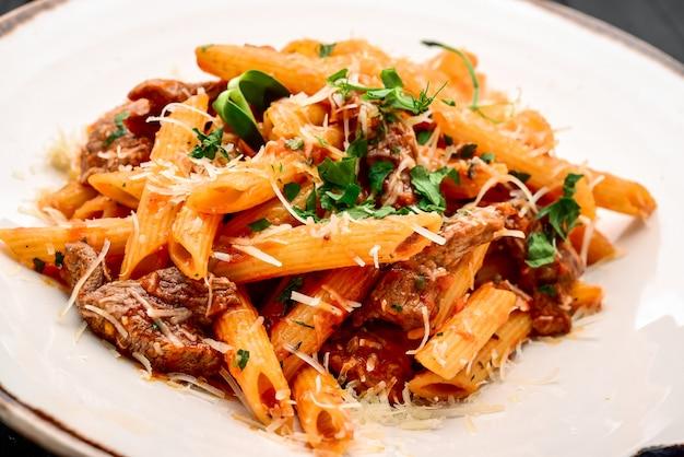 レストランのテーブルに子牛肉、トマトソース、チーズのパスタ