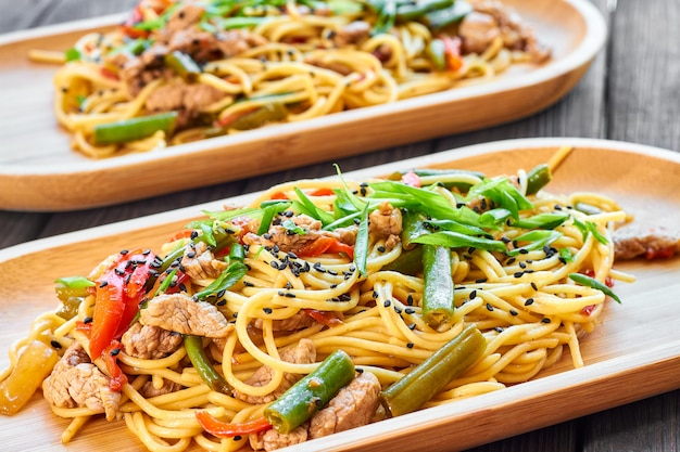 Pasta with veal and vegetables on a wooden background in a bamboo plate