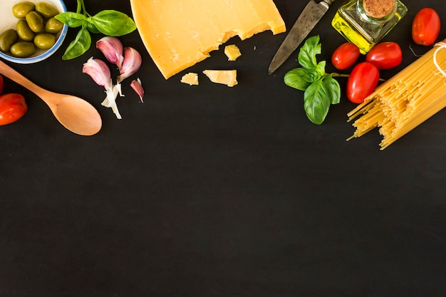 Pasta with vegetables and cheese on black background