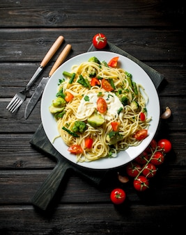 Pasta with vegetables on a plate and cherry. on black wooden background