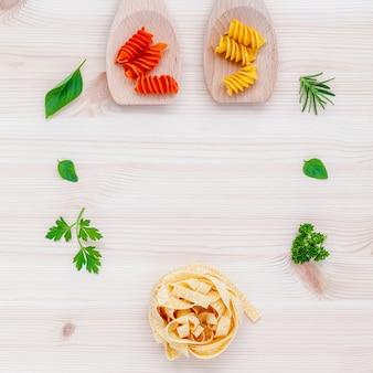 Pasta with vegetables on wooden background.
