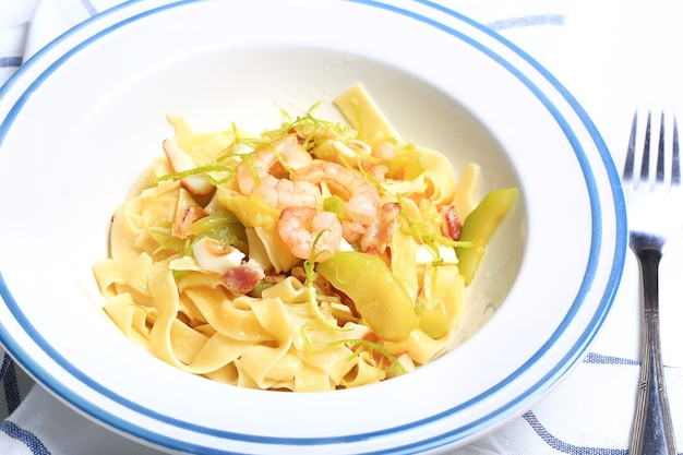 Pasta with zucchini and seafood in a white plate with a fork on a kitchen cloth on white background