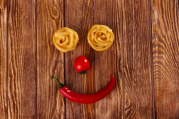 Pasta on wooden background with tomato and pepper top view