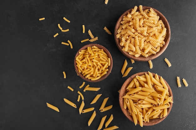 Pasta in wooden cups on black surface, top view.