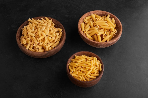 Pasta in wooden cups in the center on black surface.
