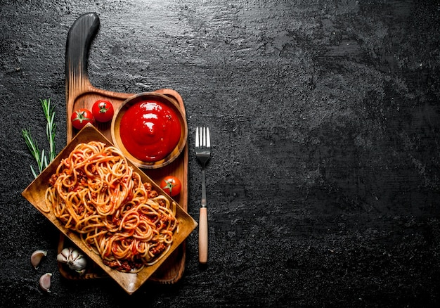 Pasta on a wooden plate with tomato sauce in bowl and rosemary. on black rustic