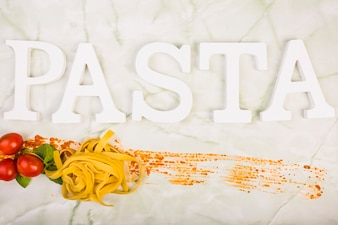 Pasta word with cherry tomato and basil leaf