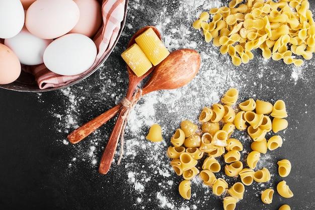 Pasta sulla farina con uova intorno.