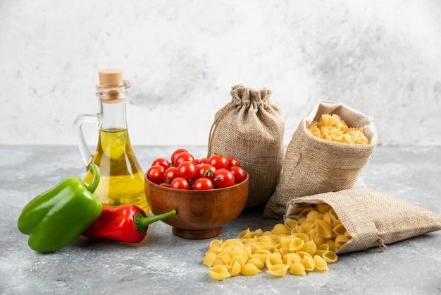 素朴な袋に入ったパスタにチェリートマト、唐辛子、オリーブオイルを添えて。