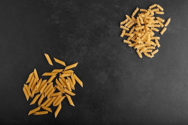 Pastas isolated on black background in opposite corners.