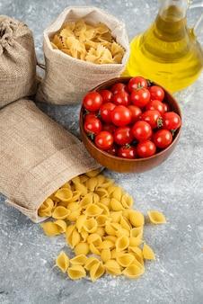 Pasta servita con pomodorini e una bottiglia di olio extra vergine di oliva.