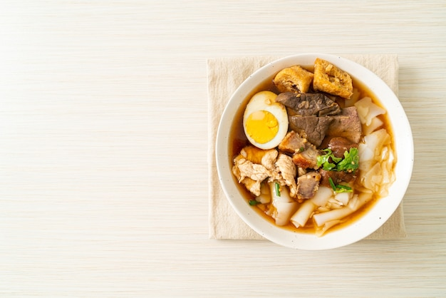 Паста из рисовой муки или отварная китайская паста квадратная со свининой в коричневом супе - азиатский стиль еды
