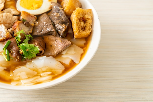 Paste of rice flour or boiled chinese pasta square with pork in brown soup - asian food style