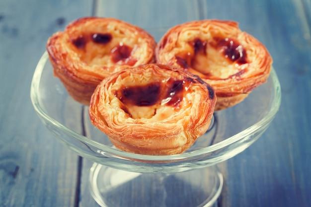 青い木製の表面に白い皿に伝統的なポルトガルのクッキーpasteisデナタ