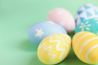 Pastel and colorful easter eggs on green background