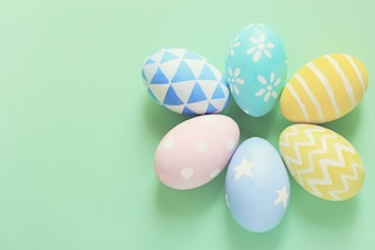 Pastel and colorful easter eggs with copy space on green background