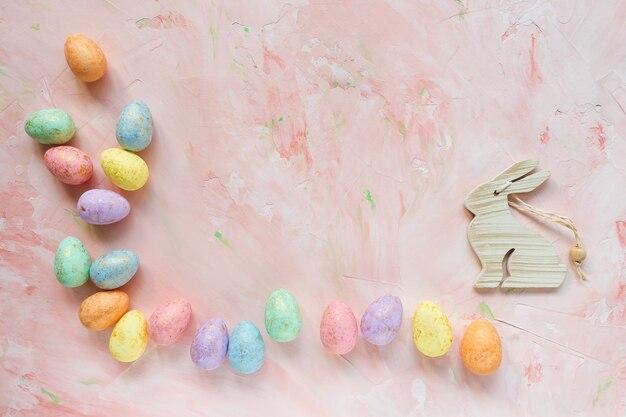 Пастельные и золотые яйца и кролик на розовом