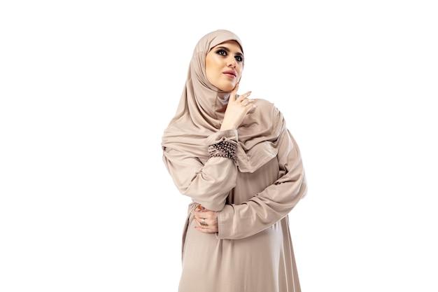 パステル。スタイリッシュなヒジャーブでポーズをとる美しいアラブの女性は、ファッション、美しさ、スタイルのコンセプトを分離しました。トレンディなメイク、マニキュア、アクセサリーを備えた女性モデル。