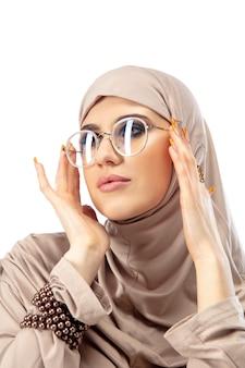 パステル。と壁に隔離のスタイリッシュなヒジャーブでポーズをとる美しいアラブの女性。ファッション、美容、スタイルのコンセプト。トレンディなメイク、マニキュア、アクセサリーを備えた女性モデル。