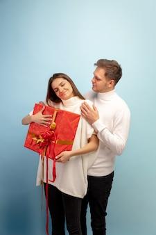 Пастель. красивая влюбленная пара на синем фоне студии. день святого валентина, концепция любви, отношений и человеческих эмоций. copyspace. молодой мужчина и женщина вместе выглядят счастливыми.