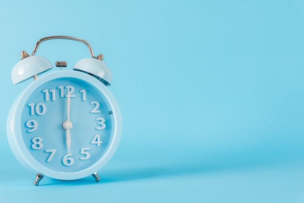 Pastel blue alarm clock with six o'clock on blue background. 6 am, 6 pm.