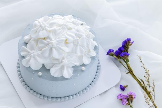 Пастельно-голубой кокосовый торт, украшенный белыми цветами из свежих сливок на белой ткани. самодельный и минимальный торт