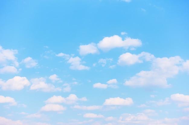 明るい白い雲とパステルブルーの春の空-自然な背景