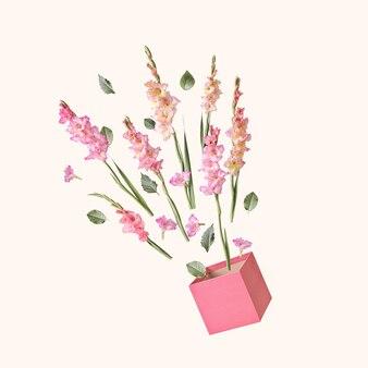 グラジオラスの花のパステルブーケがギフトボックスから飛び出します。お祝いと挨拶の概念。