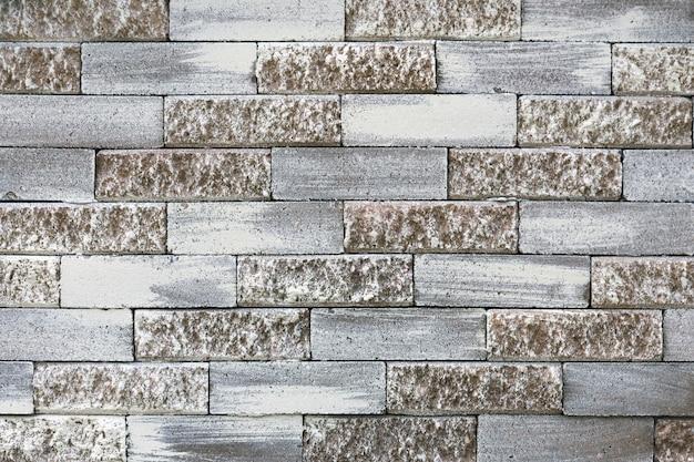 パステルレンガの壁灰色と薄茶色の石積みパターンセメントブロック塗装テクスチャグランジ建築要素抽象的な背景建物ファサード都市デザイン通りに面したタイル