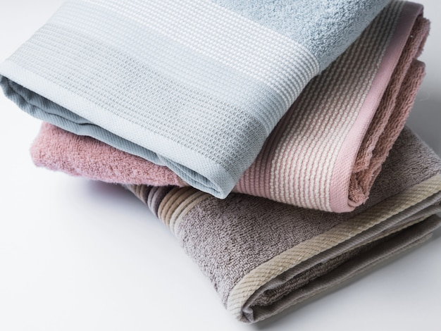 Pastel color clean folded towels on white