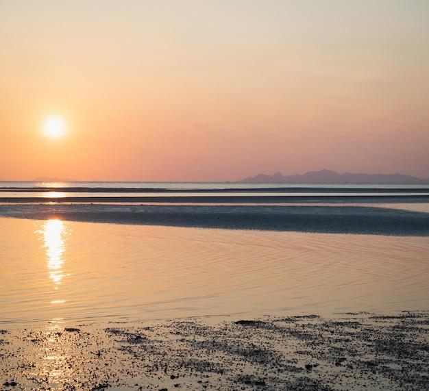 朝の空と海のビーチのパステルカラー、周りに輝く日の出の反射、シルエットスタイル、自然の美しさ