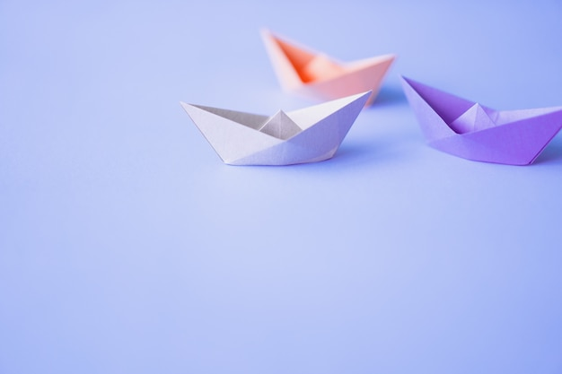 Pastel color paper boat on clean background with copy space