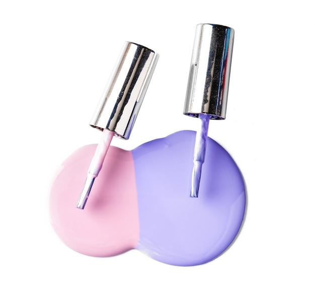Пастельные цвета пролитой бутылки лака для ногтей на белой поверхности