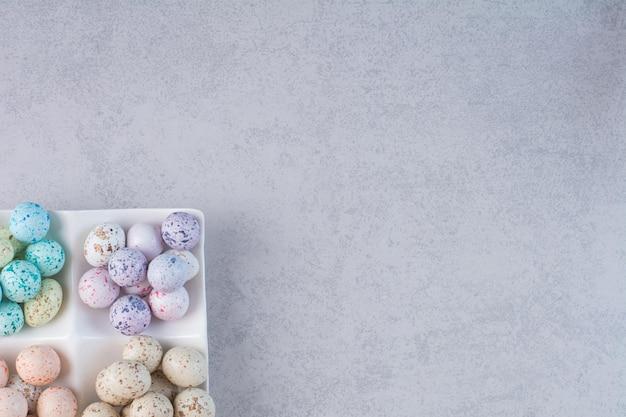 Pietre color pastello per la lavorazione su fondo in cemento.
