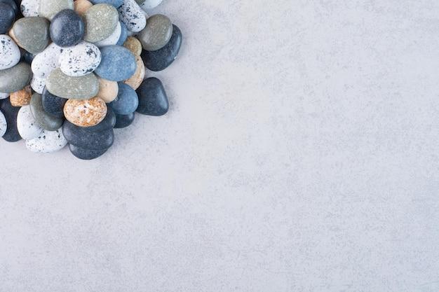 コンクリートの背景にクラフト用のパステルカラーの石。