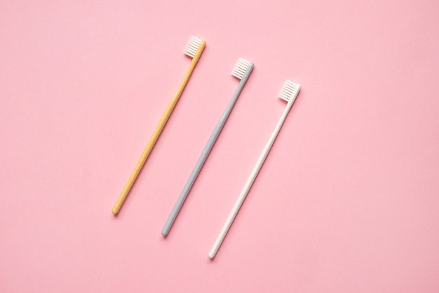 ピンクの背景にパステルカラーの歯ブラシ。歯のクリーニングと朝のルーチンの上面図のためのシンプルな構成