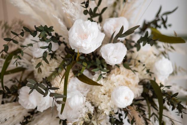 白い花と乾いたふわふわの草のパステルカラーの秋の花束。花の背景