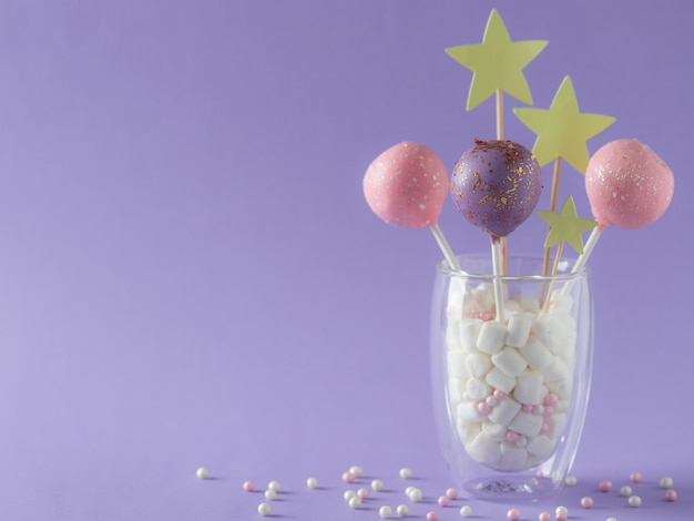 Pastel colored cake pops in a glass with marshmallows and sprinkles. birthday festive dessert. purple wall. horizontal image. place for text.