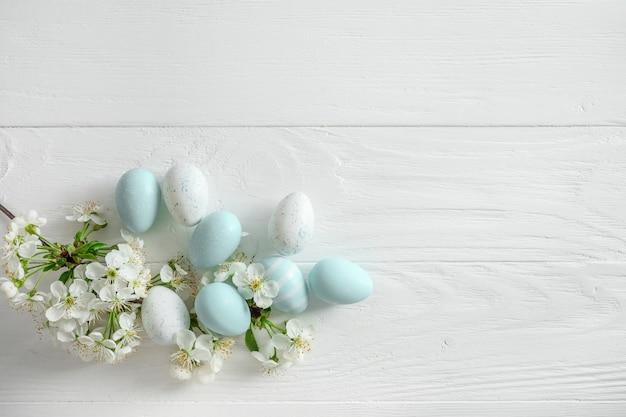 パステルカラーのイースターエッグと白い木製の春咲く枝