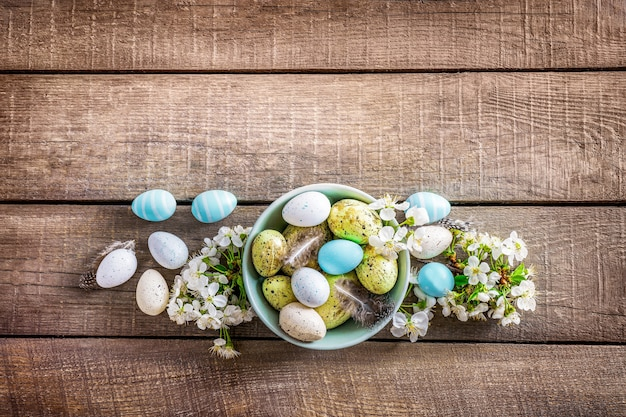 Pastel colored easter eggs in bowl and spring blooming branches on white wooden