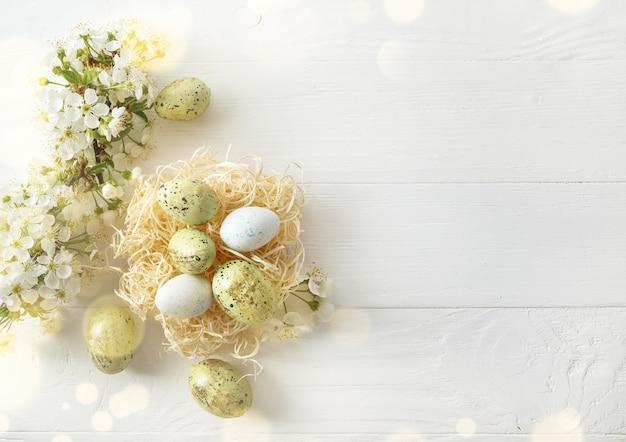 巣のパステルカラーのイースターエッグと白い木の春に咲く枝