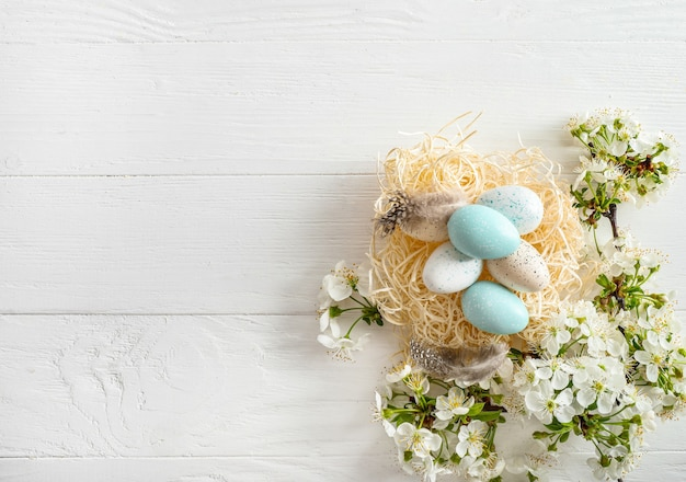 Pastel colored easter eggs in nest and spring blooming branches on white wooden
