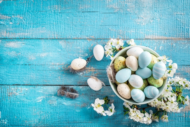 Pastel colored easter eggs and spring blooming branches on blue wooden.