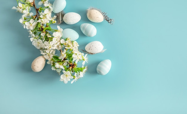 Pastel colored easter eggs and spring blooming branches on blue.