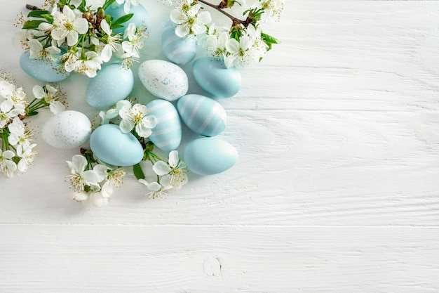 Pastel colored easter eggs and spring blooming branches on white wooden