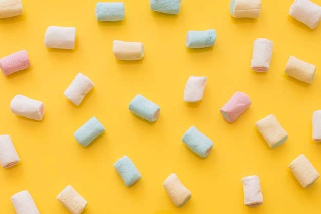 Pastel colored marshmallow on yellow background