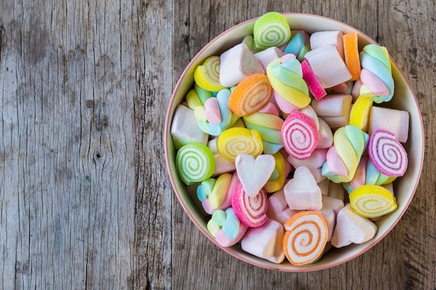 Pastel and colorfu of marshmallow and gummy candy in a wooden bowl on wooden table.