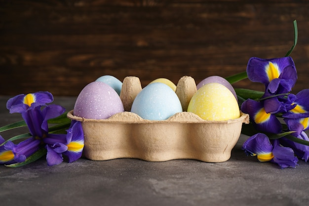 Pastel colorful easter eggs in a cardboard box and fresh flowers on a wooden background.