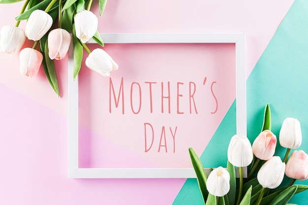 Pastel colours background with picture frame and tulip flowers flat lay patterns.