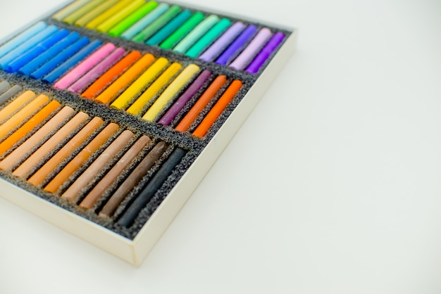 Pastel crayons in open box on a white background, top view.